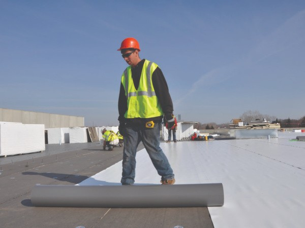 Single ply roof membrane being installed.